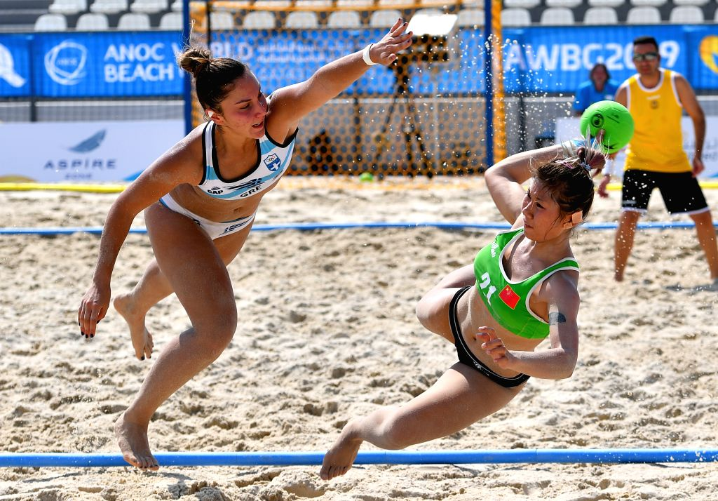 DOHA, Oct. 12, 2019 - Han Xinru (R) of China vies with Eleni Ioanna Kerlidi (L) of Greece during the women's beach handball preliminary round Group B match between China and Greece at the 1st ANOC ...