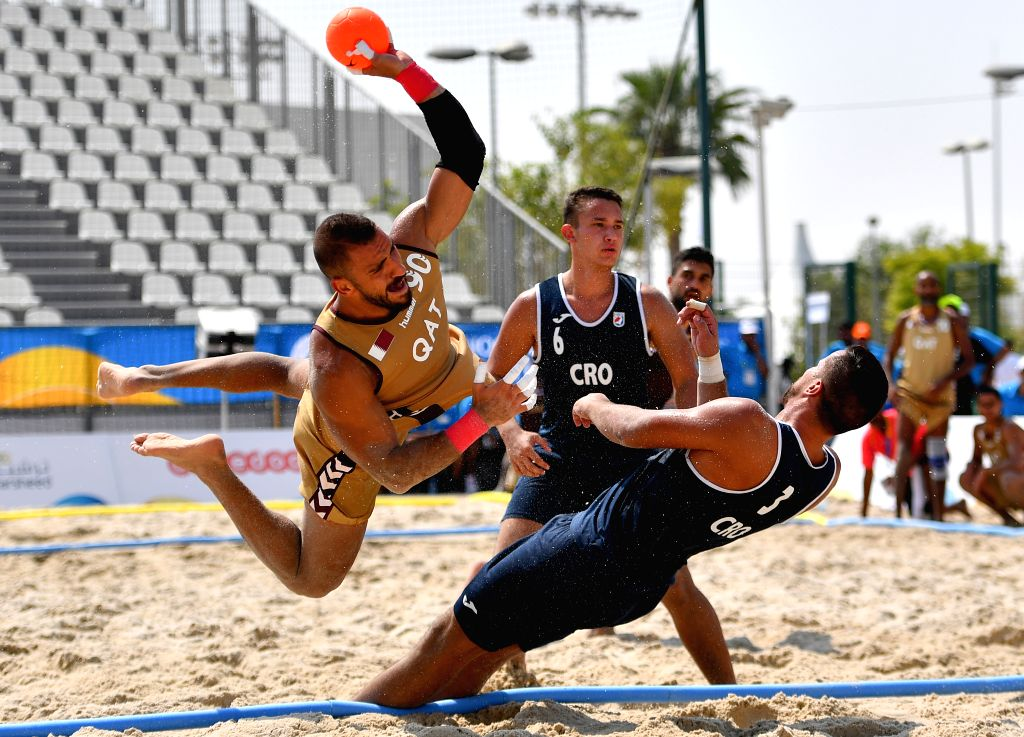DOHA, Oct. 12, 2019 - Hani Kakhi (L) of Qatar vies with Tomislav Laus (R) of Croatia during the men's beach handball preliminary round Group B match between Qatar and Croatia at the 1st ANOC World ...