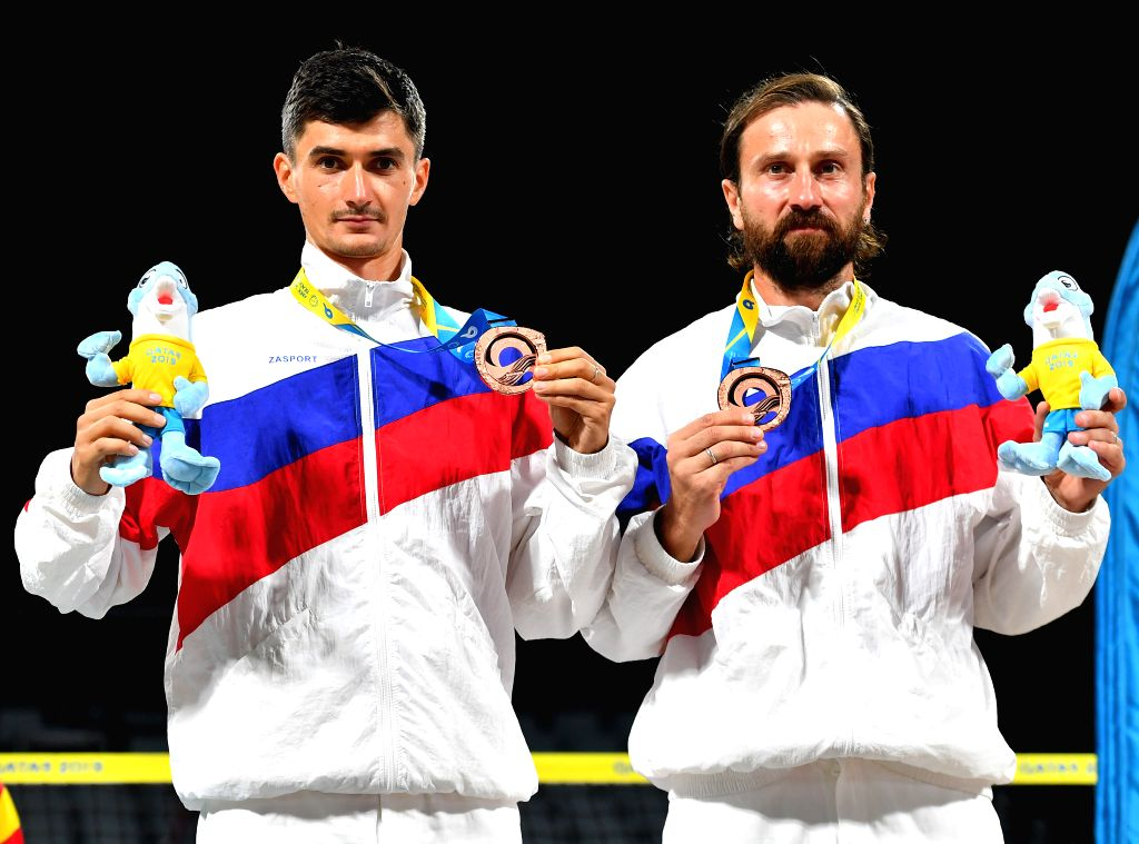 DOHA, Oct. 16, 2019 - Bronze medalists Nikita Burmakin (L)/Sergey Kuptsov of Russia pose for photos during the awarding ceremony of the men's doubles of beach tennis at the 1st ANOC World Beach Games ...