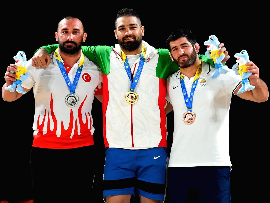 DOHA, Oct. 16, 2019 - Silver medalist Ufuk Yilmaz of Turkey, gold medalist Pouya Rahmani of Iran and bronze medalist Mamuka Kordzaia of Georgia (from L to R) pose for photos during the awarding ...