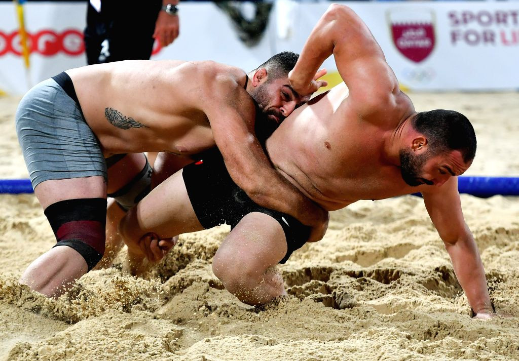 DOHA, Oct. 16, 2019 - Ufuk Yilmaz of Turkey competes against Pouya Rahmani (L) of Iran during the men's beach wrestling over 90kg final at the 1st ANOC World Beach Games Qatar 2019 in Doha, capital ...
