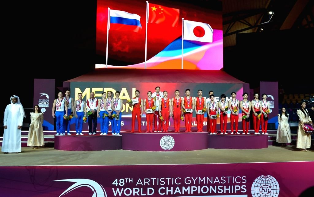 DOHA, Oct. 30, 2018 - Team China (C), Team Russia (L) and Team Japan pose on the podium after the Men's Team Final at the 2018 FIG Artistic Gymnastics Championships in Doha, capital of Qatar, Oct. ...