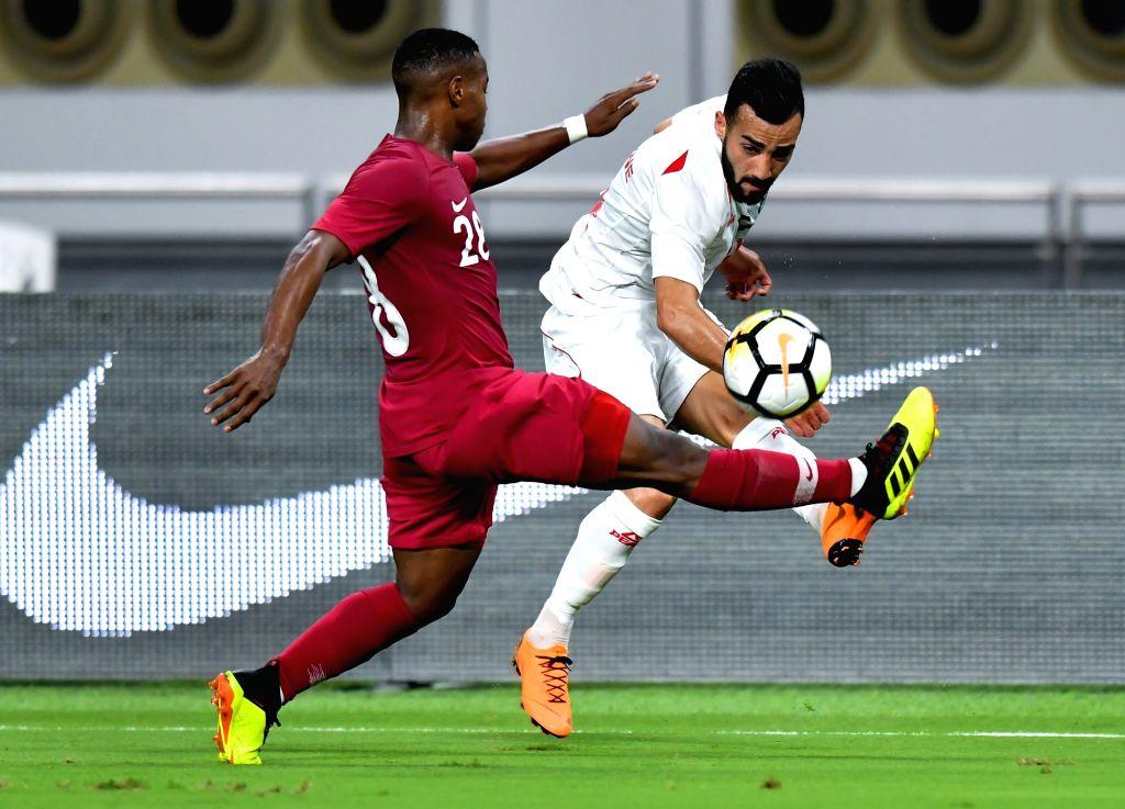 DOHA, Sep. 12, 2018 - Abdallah Gaber (R) of Palestine vies with Assim Madibo of Qatar during an international friendly soccer match between Qatar and Palestine at the Khalifa International Stadium in ...