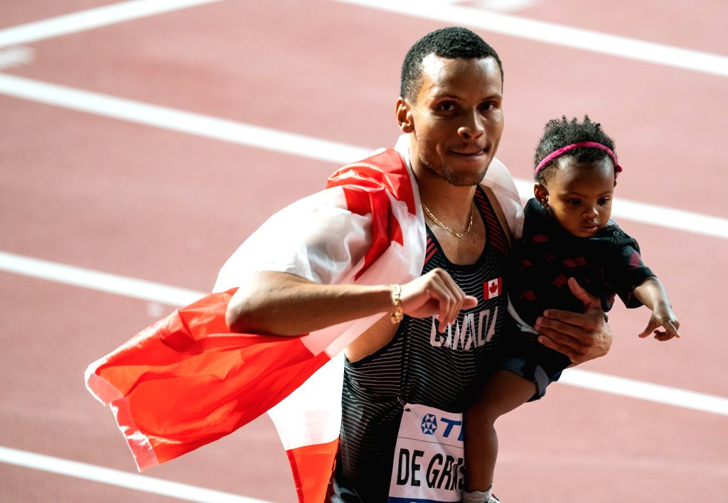 DOHA, Sept. 29, 2019 - Bronze medalist Andre De Grasse of Canada greets the audience while holding his daughter after the men's 100m final at the 2019 IAAF World Athletics Championships in Doha, ...