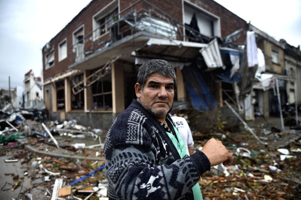 DOLORES, April 17, 2016 - A man walks in front of damage buildings after a tornado in Dolores, Uruguay, on April 16, 2016. A tornado thrashed the city of Dolores, western Uruguay, on Friday, leaving ...