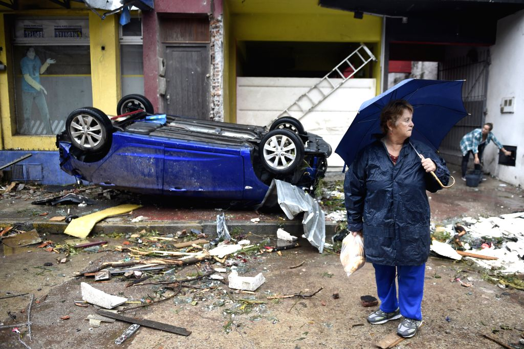 DOLORES, April 17, 2016 - A woman stands in front of an overturned car after a tornado in Dolores, Uruguay, on April 16, 2016. A tornado thrashed the city of Dolores, western Uruguay, on Friday, ...