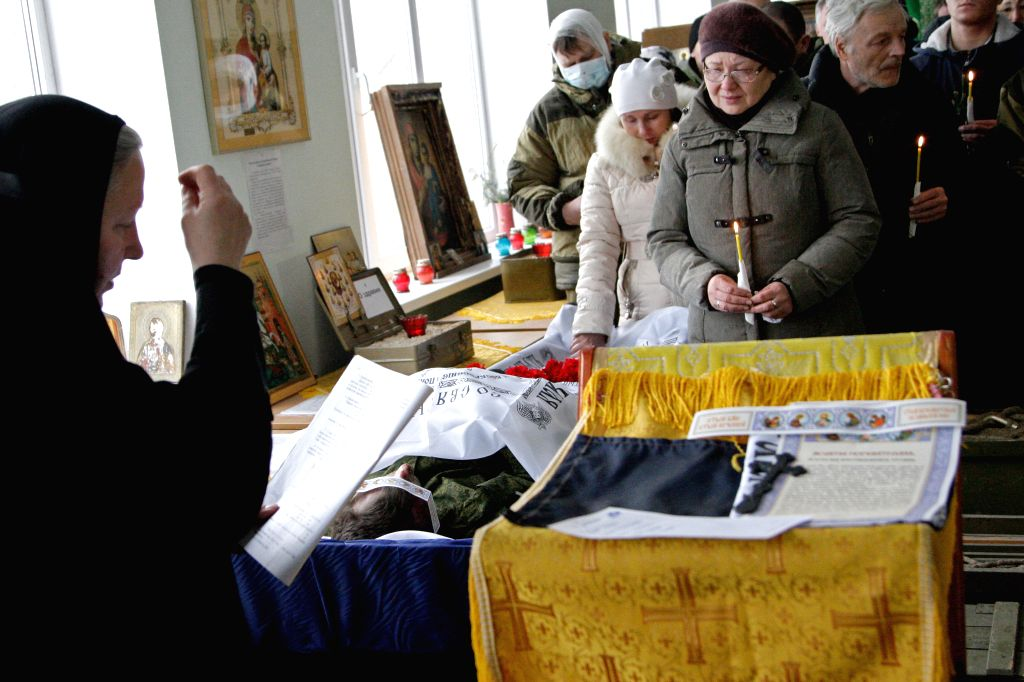 Relatives and friends attend the funeral of two local militias, who was killed in fightings with Ukrainian troops near Debalcevo in Donetsk, Ukraine, on Feb. 16, ...