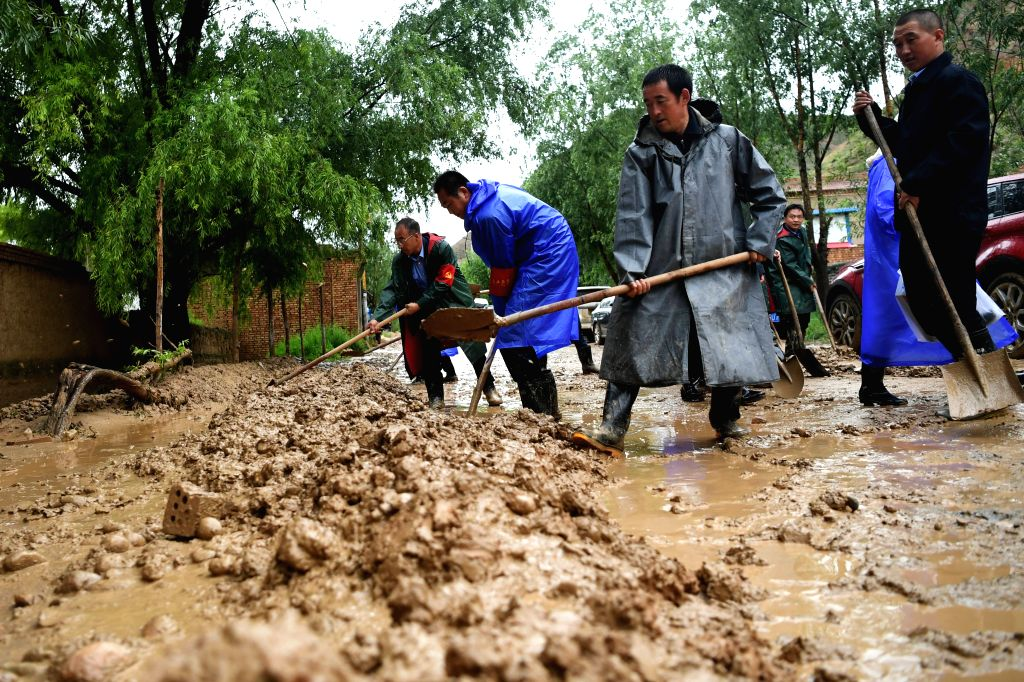 DONGXIANG, July 20, 2018 - People clear the mud at flood-hit Chenhe Village of Dongxiang Autonomous County in Linxia Hui Autonomous Prefecture, northwest China's Gansu Province, July 20, 2018. About ...