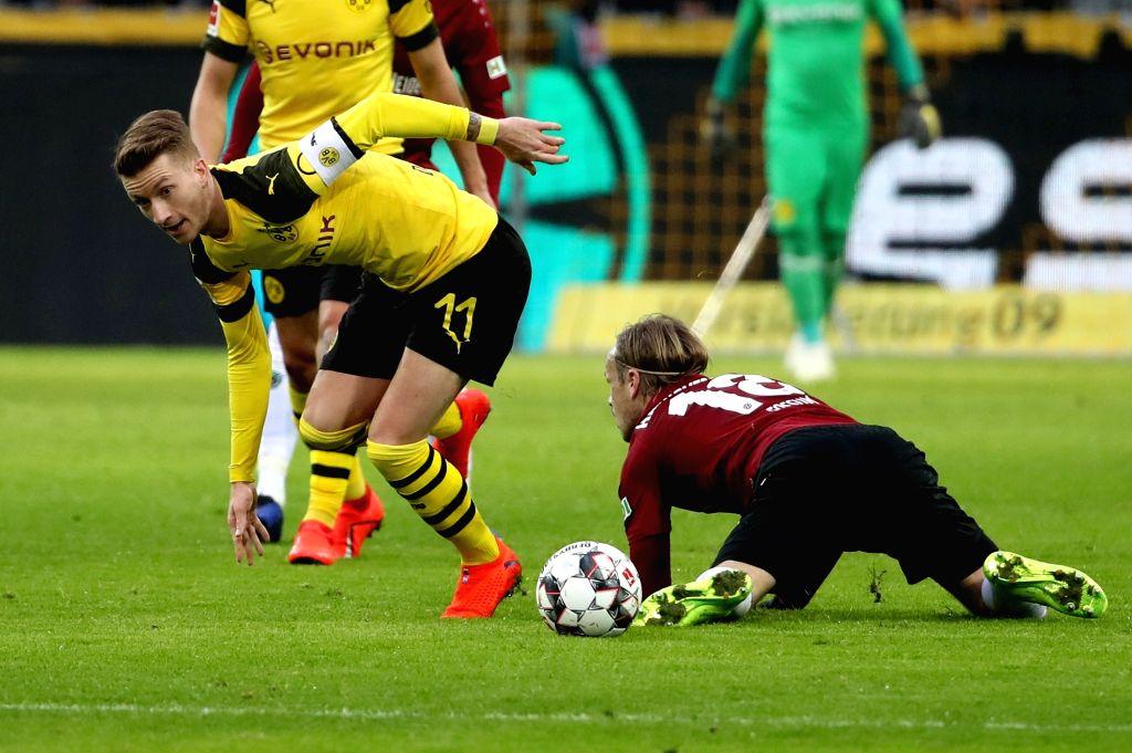 DORTMUND, Jan. 27, 2019 - Marco Reus (L) of Dortmund vies with Iver Fossum of Hannover during the Bundesliga match between Borussia Dortmund and Hannover 96 in Dortmund, Germany, Jan. 26, 2019. ...