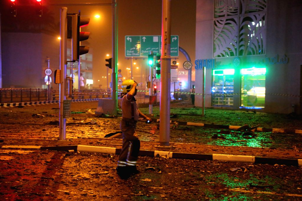 A firefighter walks by the Marina Torch which caught fire on early Saturday morning in Dubai, the United Arab Emirates (UAE), Feb. 21, 2015. The 79-story Marina ...