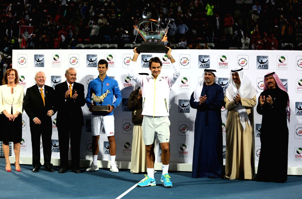 Roger Federer (C) of Switzerland poses with his trophy during the awarding ceremony of the final match against Novak Djokovic of Serbia on the fifth day of the ATP ...