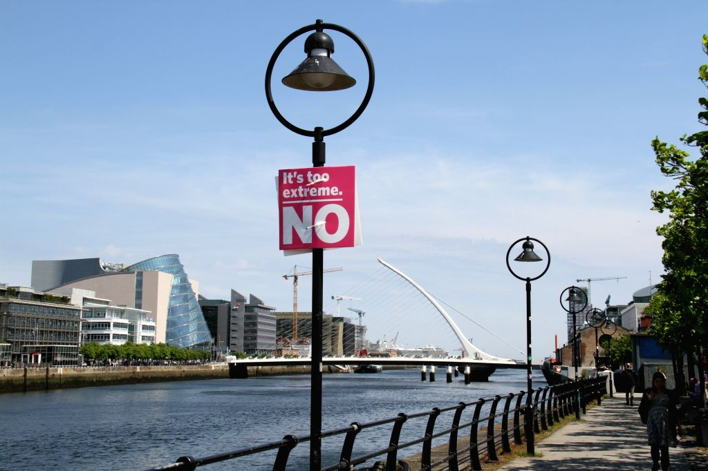 DUBLIN, May 26, 2018 - A pregnant woman passes by a lamp poster against legalized abortion along River Liffey in downtown Dublin, Ireland, May 25, 2018. Nearly 70 percent of Irish voted to abolish ...