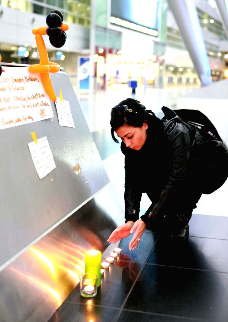 A passenger lights candles to mourn victims of the crashed plane of Germanwings at the airport in Duesseldorf, Germany, on March 24, 2015. An Airbus A320 of ...