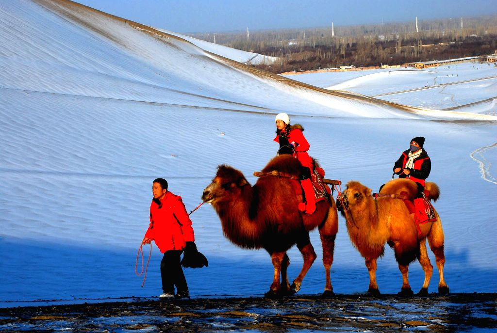 Tourists ride camels as they visit the snow-covered sand dunes of the Mingsha Mountain in Dunhuang, northwest China's Gansu Province, Jan. 17, 2015. Dunhuang saw ..