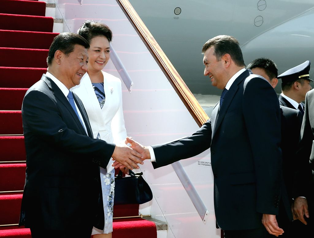 Chinese President Xi Jinping (L) and his wife Peng Liyuan arrive in Dushanbe, capital of Tajikistan, Sept. 11, 2014. Xi Jinping would attend the 14th summit of ...