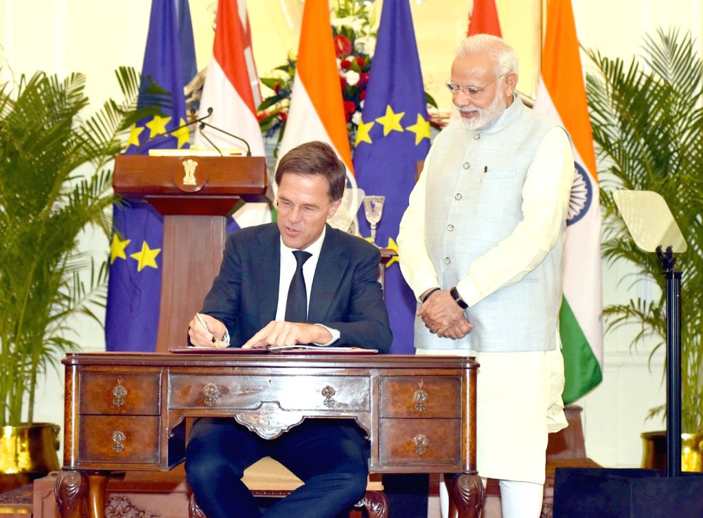Dutch Prime Minister Mark Rutte signs the visitors book of Hyderabad House while Prime Minister Narendra Modi looks on, in New Delhi on May 24, 2018. - Mark Rutte and Narendra Modi