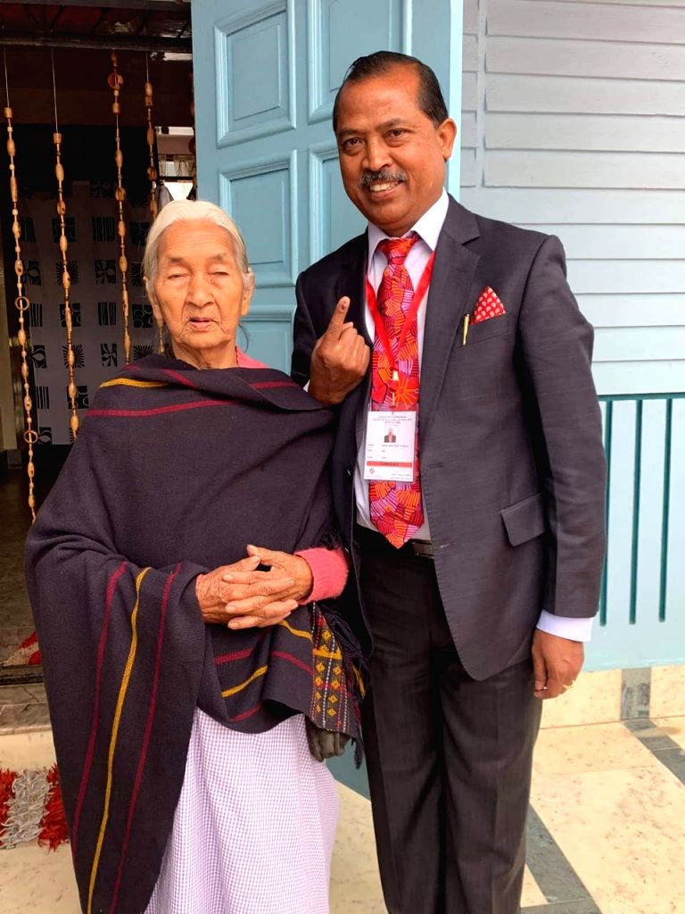 East Jaintia Hills (Meghalaya): Congress MP and the party's Lok Sabha candidate from Shillong seat, Vincent Pala accompanied by his mother Hermelinda Pala, shows his inked finger after casting his vote for the 2019 Lok Sabha elections, at Lamyrsiang