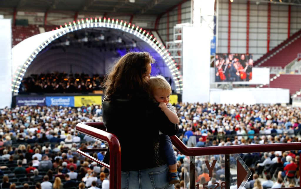 EDINBURGH, Aug. 2, 2019 - A mother with her baby in arms enjoys music during the LA Phil's performance at the Edinburgh International Festival opening event in Edinburgh, Britain, on Aug. 2, 2019. ...
