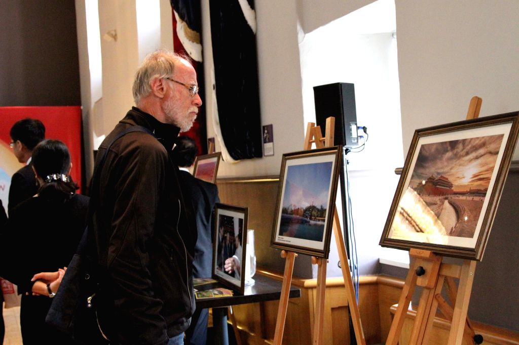 EDINBURGH, June 28, 2016 - A visitor looks at a picture at the Beijing tourism photo show in Edinburgh, Britain, on June 27, 2016. A grand photo show was held on Monday inside the famous tourist ...