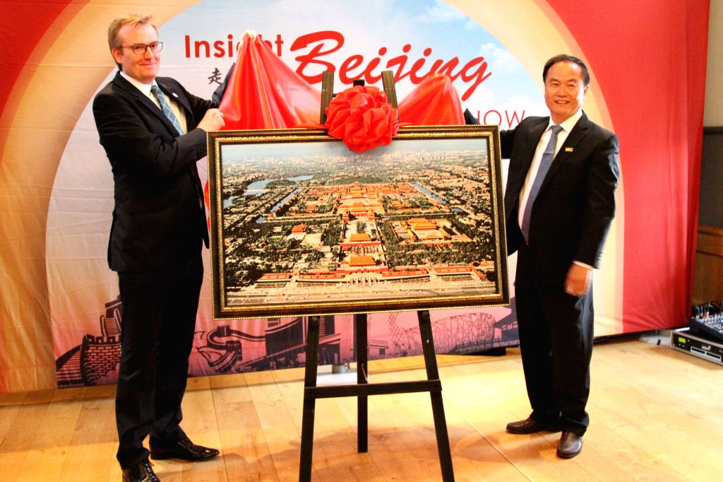 EDINBURGH, June 28, 2016 - Song Yu (R), head of the Beijing Municipal Commission of Tourism Development, and Neil Brownlee, head of Business Tourism at VisitScotland, unveil the Beijing tourism photo ...
