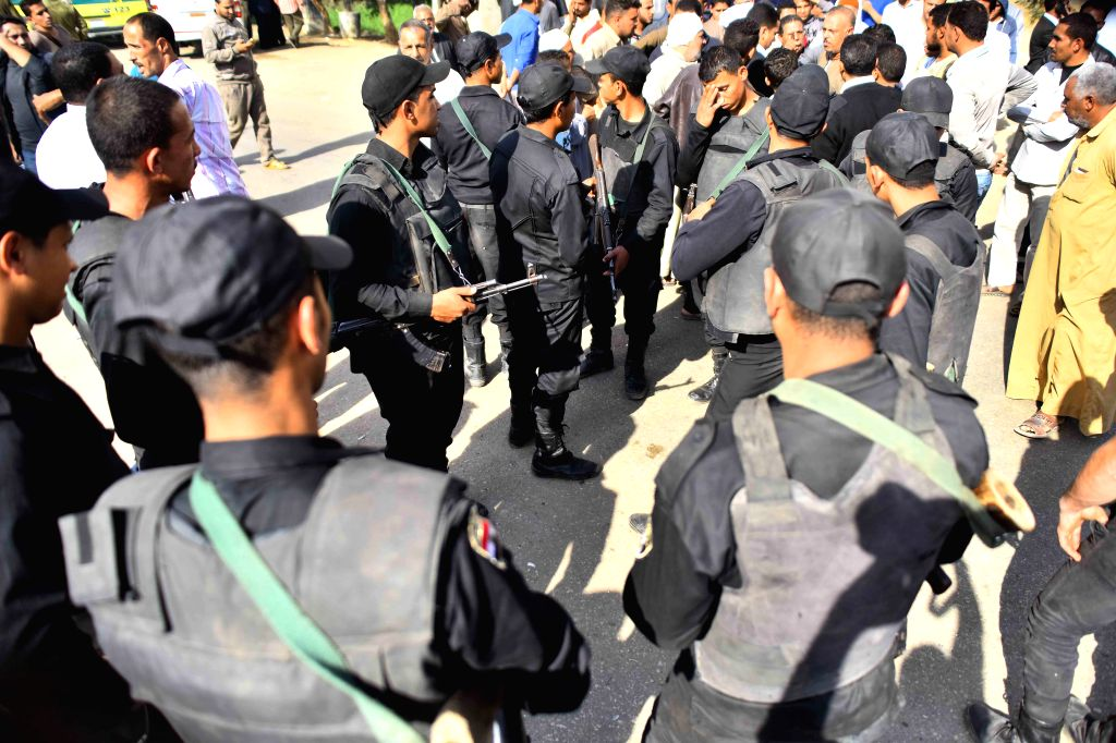 Egyptian security personnel gather on the site of an attack in Giza, Egypt, on Nov. 28, 2015. Unknown militants shot four policemen dead Saturday on the road to the ...
