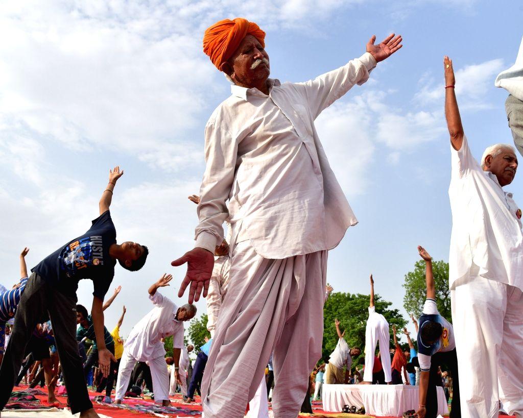 Elderly men practice Yoga Asans  -postures- on International Yoga Day in Bikaner on June 21, 2017.