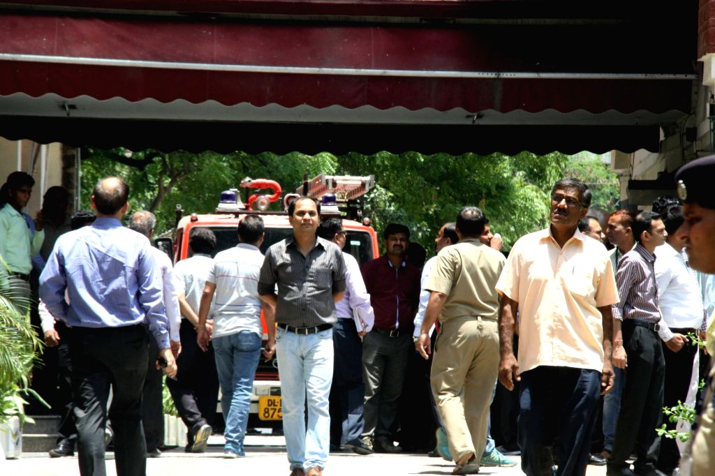 Election Commission staff come out of the building after a fire broke out in the building in New Delhi, on June 12, 2017.