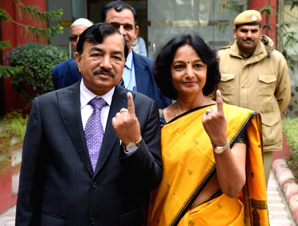 Election Commissioner Sushil Chandra and his wife show their inked fingers after casting their votes for Delhi Assembly elections 2020 at Wonderland Kids School in Delhi's New Moti Bagh on ...