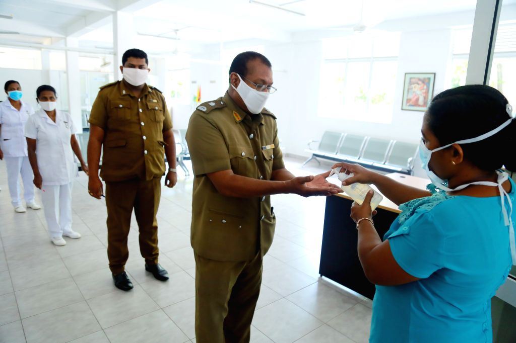Employees from Sri Lankan public and health sectors line up to have their hands sanitized during a postal voting at a polling station in Kirulapone of Colombo, Sri ...