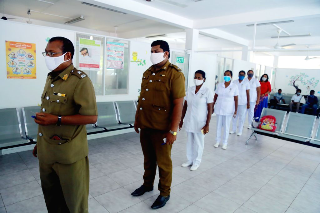 Employees from Sri Lankan public and health sectors line up during a postal voting at a polling station in Kirulapone of Colombo, Sri Lanka, on July 13, 2020. Sri ...