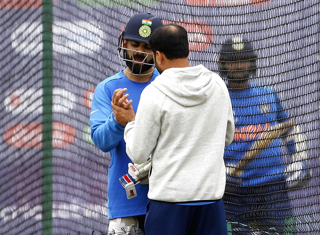 England: A member of the support staff attends to Indian skipper Virat Kohli at the nets during a practice session ahead of the 2019 World Cup match against New Zealand, at Trent Bridge Cricket Ground in Nottinghamshire, England on June 12, 2019. (Ph - Virat Kohli and Surjeet Yadav