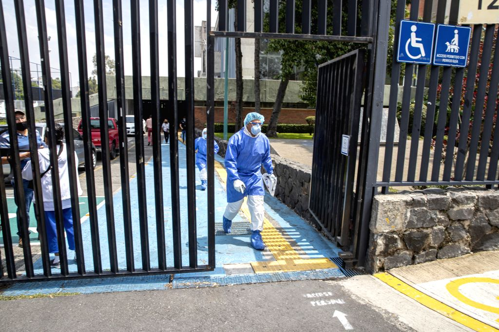 Epidemic prevention personnel walk out of a natatorium in Mexico City, Mexico, Aug. 10, 2020. Some natatoriums in Mexico City have reopened to the public with ...