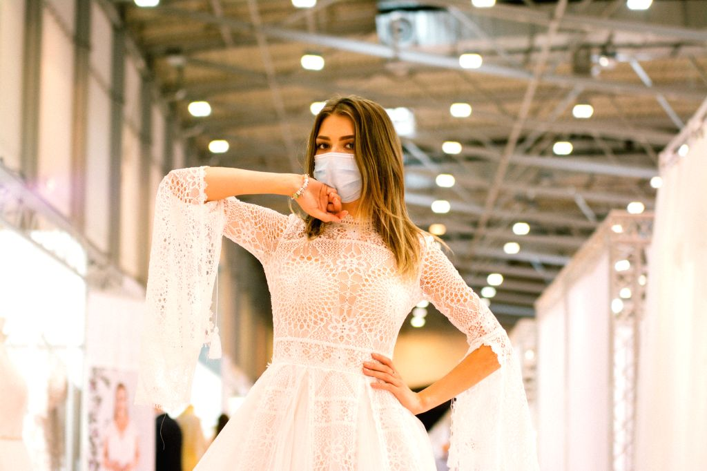 Essen (Germany), July 5, 2020 A model wearing a face mask presents a wedding dress at the European Bridal Week trade fair in Essen, Germany, July 5, 2020. The European Bridal Week, an ...