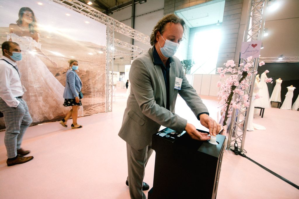 Essen (Germany), July 5, 2020 An exhibitor wearing a face mask sanitizes his hands at the European Bridal Week trade fair in Essen, Germany, July 5, 2020. The European Bridal Week, an ...