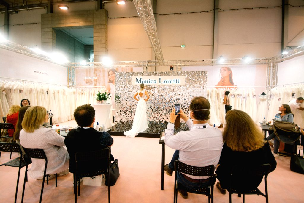 Essen (Germany), July 5, 2020 Visitors watch a model presenting a wedding dress at the European Bridal Week trade fair in Essen, Germany, July 5, 2020. The European Bridal Week, an ...
