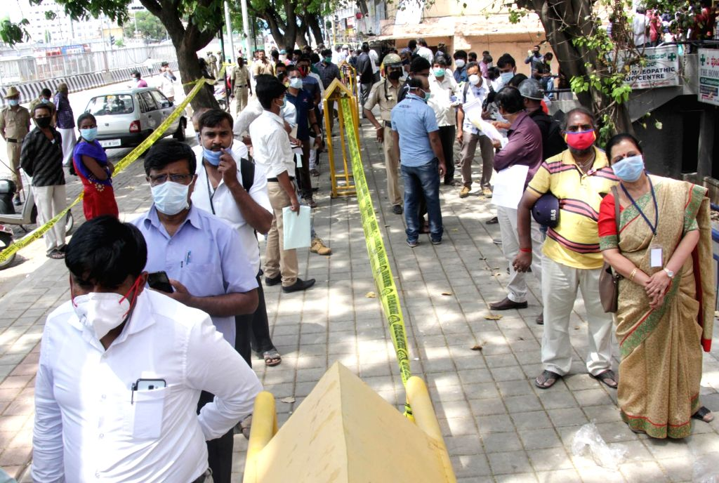 Essential service providers queue up to collect passes on Day 2 of the 21-day nationwide lockdown imposed by the Narendra Modi government over the coronavirus pandemic; in Bengaluru on ... - Narendra Modi