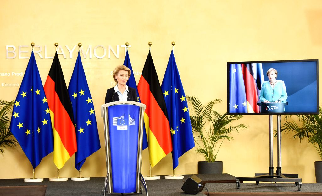 European Commission President Ursula von der Leyen (L) and German Chancellor Angela Merkel (on the screen) attend a video press conference at the European ...