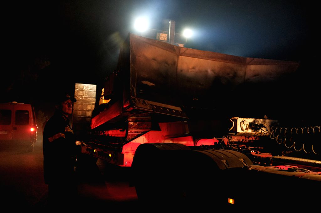 EVIA, Aug. 14, 2019 - A grader truck is moved to the front of the raging blaze near Makrymalli village on Evia island, Greece, on Aug. 13, 2019. The central part of Greece's Evia island was declared ...