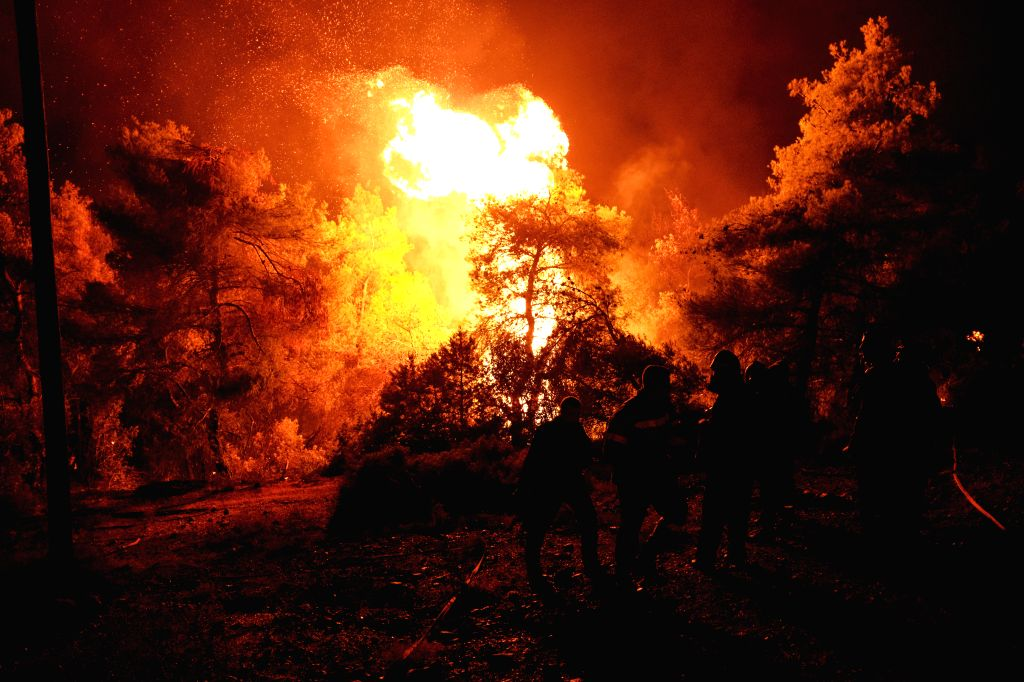 EVIA, Aug. 14, 2019 - Fire fighters battle a blaze raging near Makrymalli village on Evia island, Greece, on Aug. 13, 2019. The central part of Greece's Evia island was declared in state of emergency ...