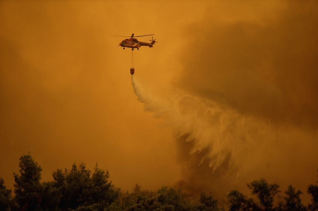 EVIA ISLAND, Aug. 13, 2019 - A water-dropping helicopter is seen battling a wildfire near Makrymalli village on Evia island, Greece, Aug. 13, 2019. Greek fire fighters were battling the largest ...