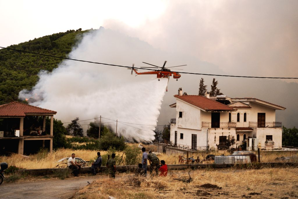 EVIA ISLAND (GREECE), Aug. 13, 2019 A water-dropping helicopter is seen battling a wildfire near Makrymalli village on Evia island, Greece, on Aug. 13, 2019. Greek firefighters battled ...