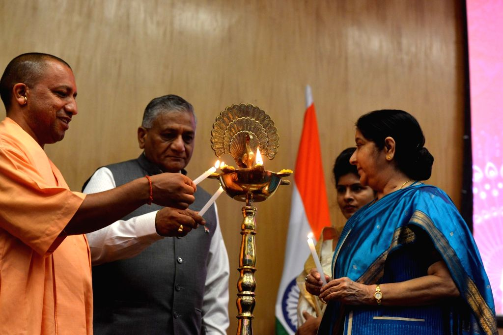 External Affairs Minister Sushma Swaraj, MoS External Affairs V.K. Singh and Uttar Pradesh Chief Minister Yogi Adityanath light the inaugural lamp at the launch of the website for 15th ... - Sushma Swaraj and K. Singh