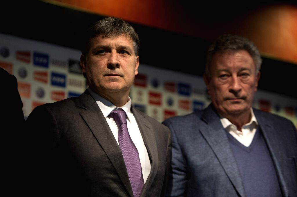 Gerardo Martino (L) reacts during a press conference for his official presentation as the new head coach of the Argentina's national soccer team in the campus of the