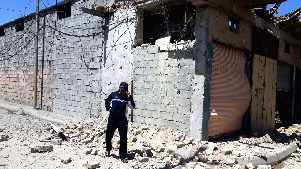 A man stand by a damaged building after an Iraqi Air Force bombing in Islamic State (IS) militants-seized city of Fallujah, some 50 km west of Baghdad, Iraq, April ...