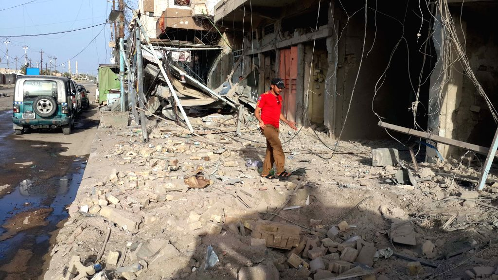 A man stands by a damaged building after Iraqi Air Force's bombing in Islamic State (IS) militants-seized city of Fallujah, some 50km west of Baghdad, Iraq, April ...
