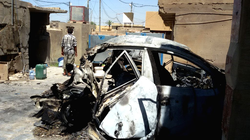 FALLUJAH, May 24, 2016 - A man stands by a damaged car which was hit by a projectile launched by the Iraqi Force against the Islamic State militants in Fallujah, Iraq, on May 24, 2016. Iraqi security ...
