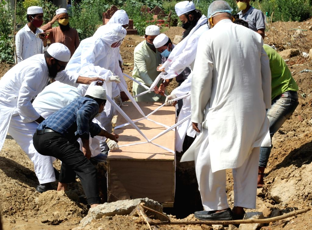 Family members carry the mortal remains of the  covid-affected victim for burial during the second wave of Covid-19 at Delhi gate graveyard in New Delhi on Saturday May 22, 2021.