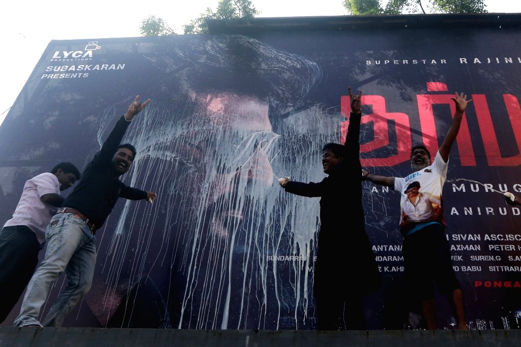 "Fans of actor Rajinikanth wash the poster of his film ""Darbar"" to celebrate the film's release, outside a theatre in Chennai on Jan 9, 2020. - Rajinikanth"