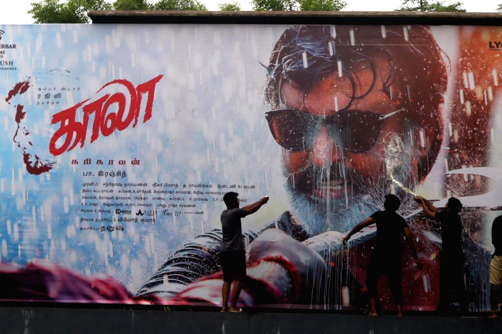 """Fans wash a poster of actor Rajinikanth with milk after release of his film """"Kaala"""" in Chennai on June 7, 2018. - Rajinikanth"""