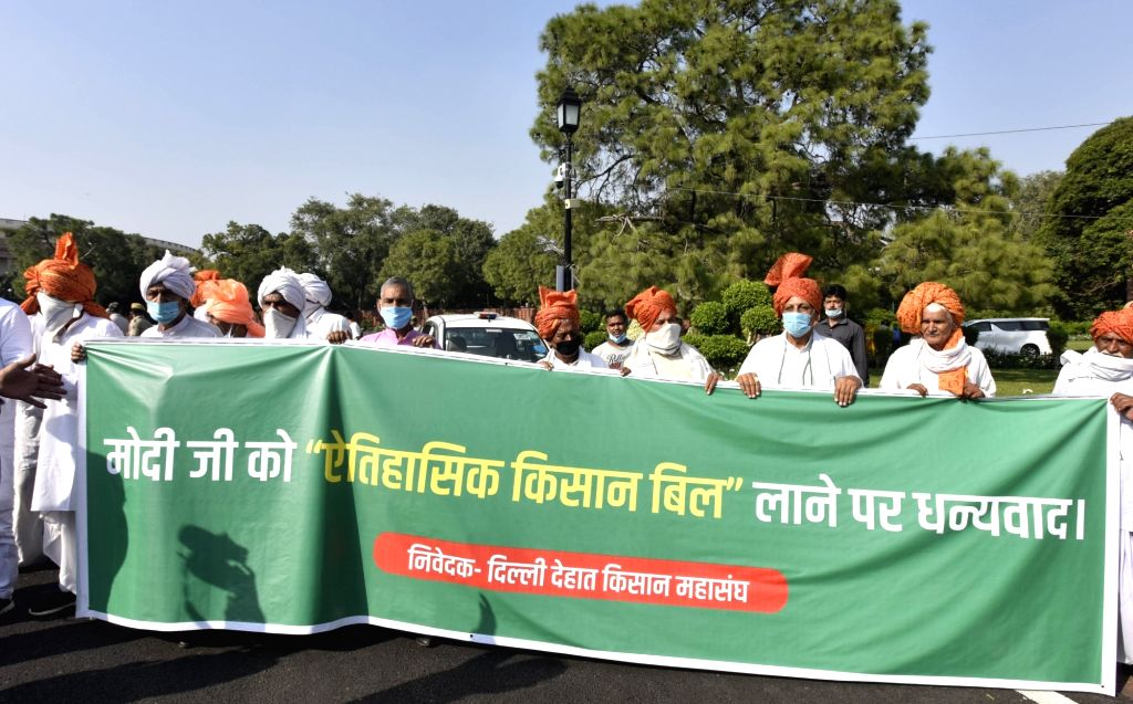 Farmers hold a banner as they celebrate after the passing of two farm bills in Rajya Sabha today during the ongoing Monsoon Session, at Vijay Chowk in New Delhi, India on  Sunday, ...